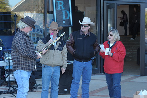 Morris employees George Cook, Lowell Dorn and Sherry Fulmer and Morris contract employee Mac Abernathy (second from right) admire trophy won by Cook riding in the truck parade.